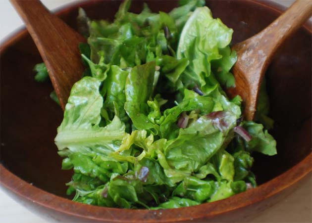 Toss the greens with vinaigrette.